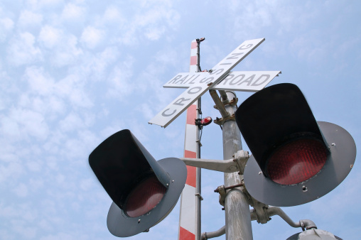 Railroad Crossing Signal Gate Lights With A Blue Sky Stock Photo - Download Image Now