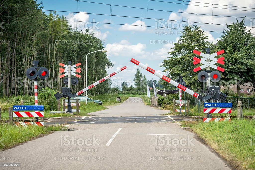 Railroad crossing with dense trees and reaching warning to royalty-free stock photo
