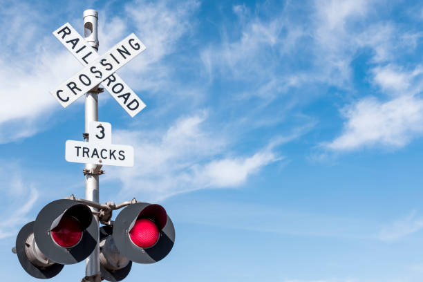 railroad crossing with wispy cloud in blue sky behind - railway signal stock photos and pictures