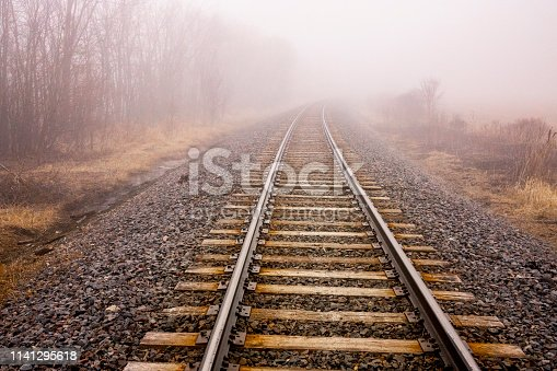 Railroad disappears into dense fog, giving true meaning to vanishing point perspective.