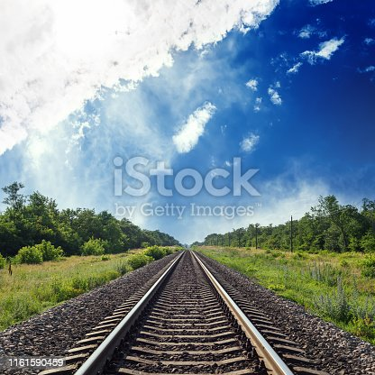 railroad in green landscape to horizon in blue cloudy sky