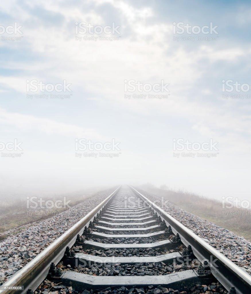 Eisenbahn in Wiese mit Nebel und Wolken drüber – Foto