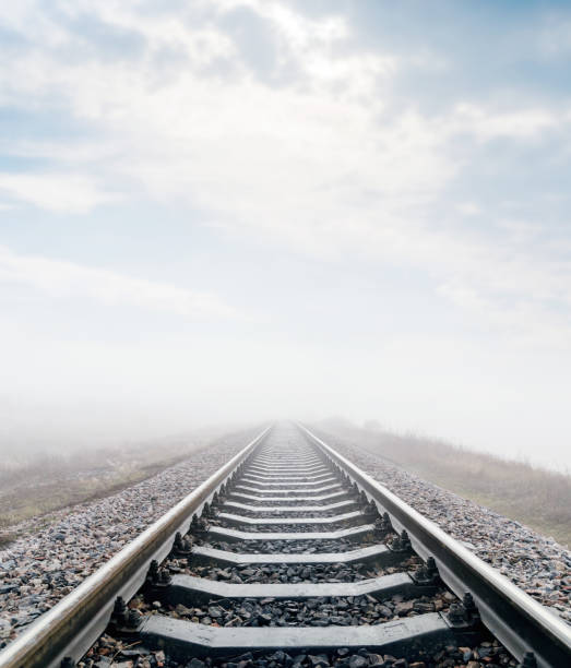 railroad in meadow with fog and clouds over it railroad in meadow with fog and clouds over it tramway stock pictures, royalty-free photos & images