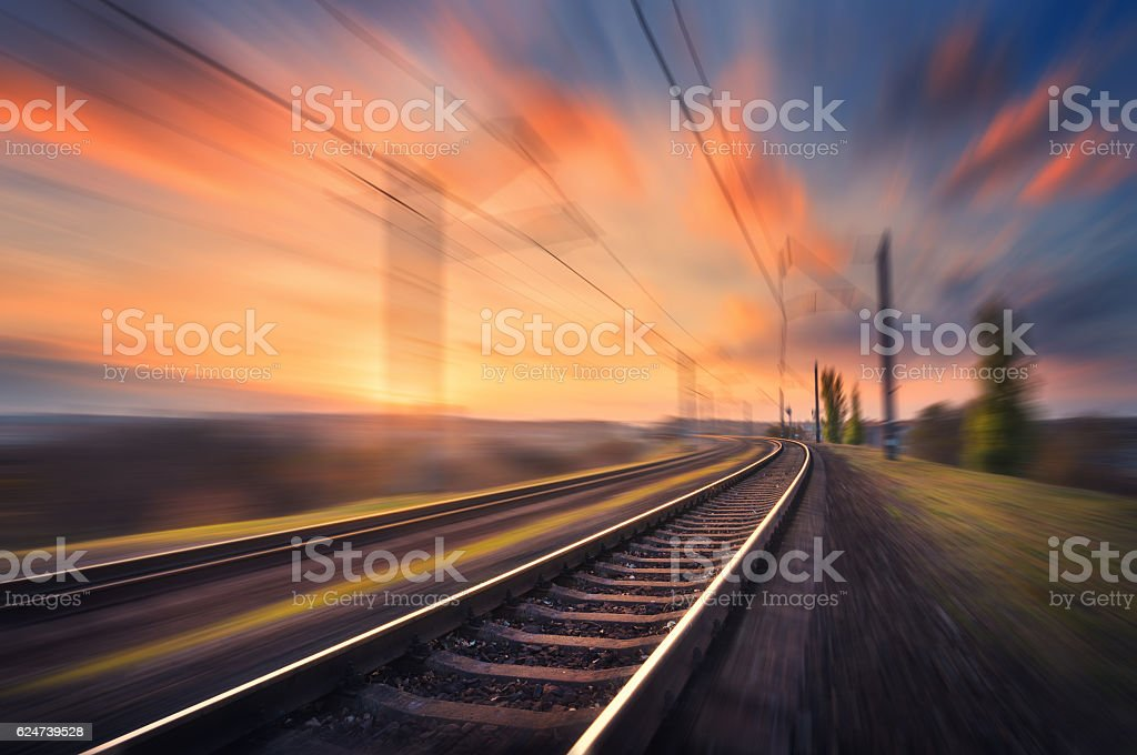 Railroad in motion at sunset. Blurred railway station stock photo