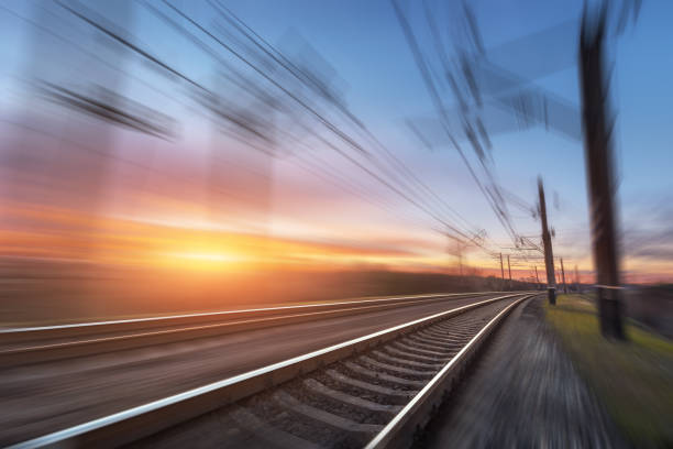 railroad in motion at sunset. railway station - rail stock photos and pictures