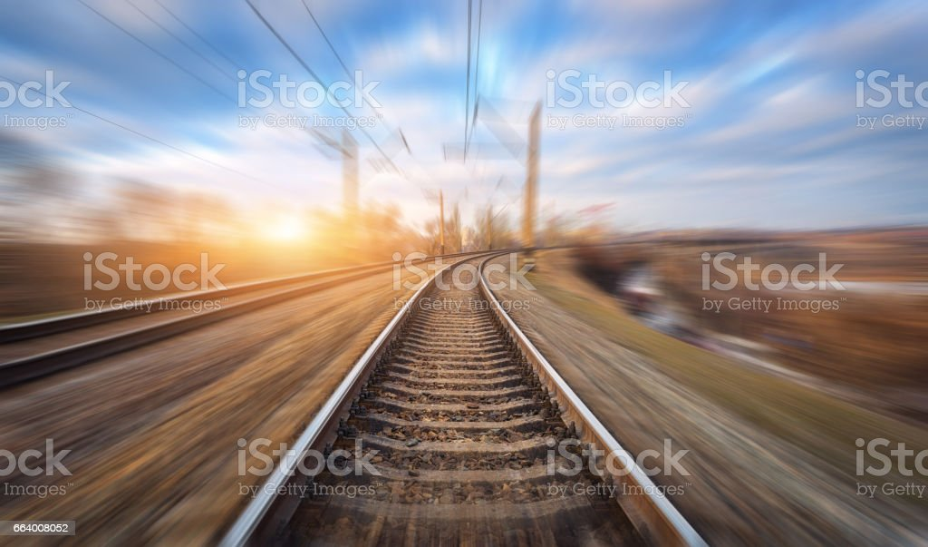 Railroad in motion at sunset. Railway station with motion blur effect and colorful sky with clouds. Industrial concept background. Railroad travel, railway tourism. Blurred railway. Transportation stock photo