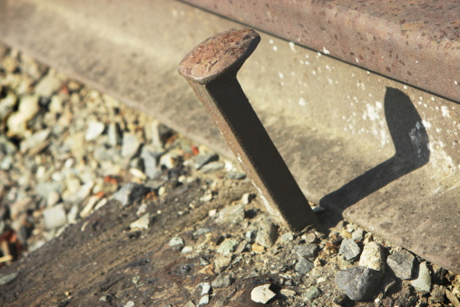 Loose rusted iron railroad spike and rail track close-up.