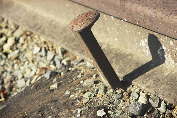 Railroad Spike Train Track Loose rusted iron railroad spike and rail track close-up. spiked stock pictures, royalty-free photos & images