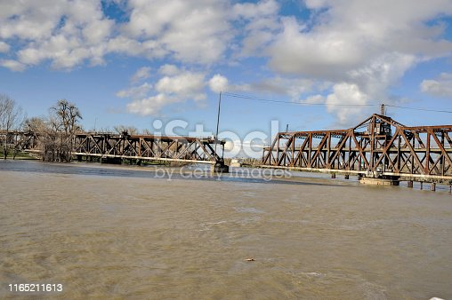 This metal swing bridge carries railroad as well as vehicles when the bridge is closed, when open larger boats can pass thru up or down the Sacramento River. Especially important with the river so swollen due to the excessing rains. Water treatment facility north of the bridge at rivers edge.