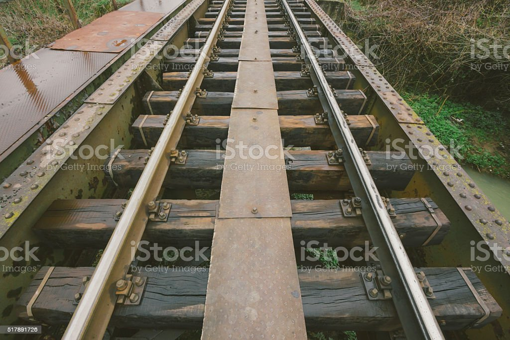 Railroad track across old, steel bridge in perspective view stock photo