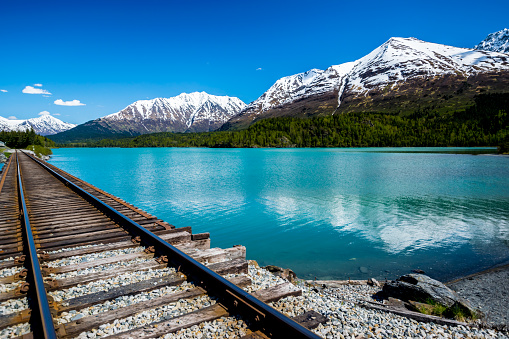 Railroad track by the turquoise Lower Trail Lake in the Chugach National Forest, Alaska, with mountain range in background