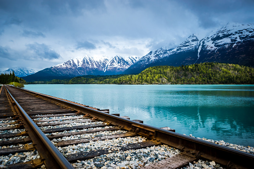 Railroad track with lake and mountain range