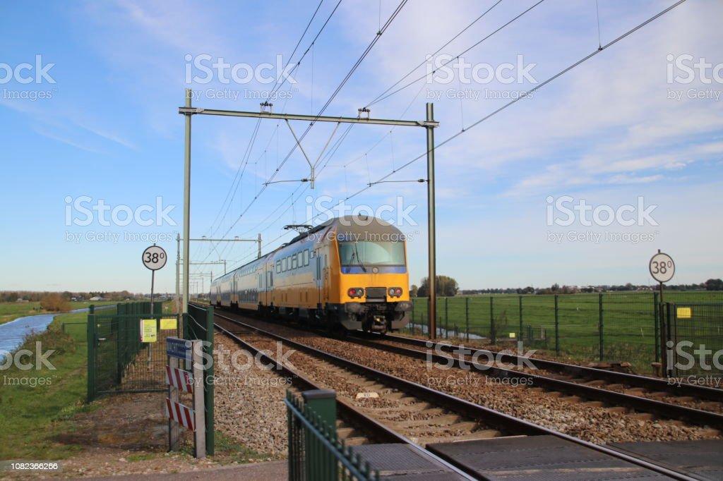 Track van de spoorweg met geel blauw Nederlandse dubbeldekker trein tussen Gouda en Rotterdam bij Moordrecht foto