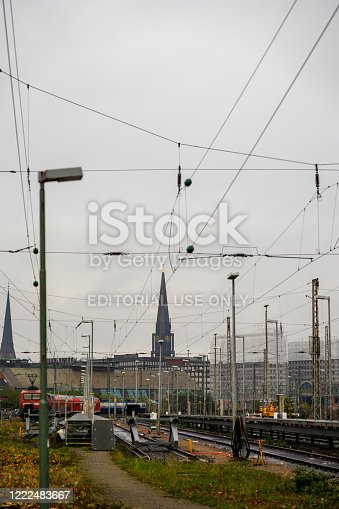Hamburg, Germany - November 9, 2019: The train arrives at an unknown subway station in Hamburg, with Hamburg city and a church in the background.