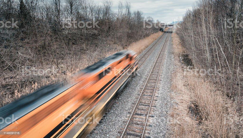 railroad tracks with train in blurred motion. Spring season, no leafs...
