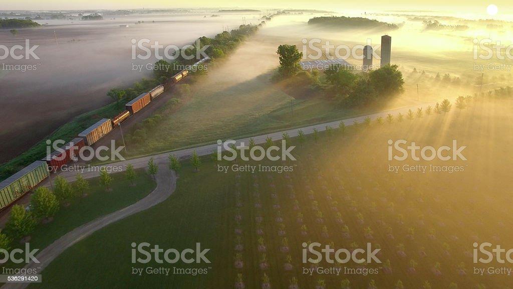 Railroad train rolls across breathtakingly beautiful, foggy landscape at sunrise stock photo