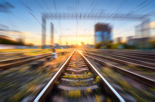 Railroad with motion blur effect at sunset. Industrial conceptual landscape with blurred railway station, buildings, green grass, blue sky and orange sunlight in the evening. Railway track. Background