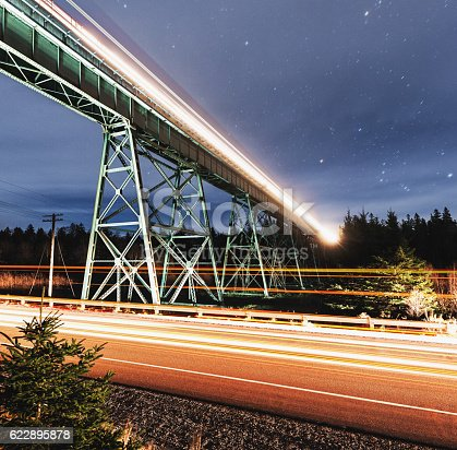 Traffic passes beneath a freight train high above on a steel trestle bridge spanning a river valley.  Long exposure with light painting.