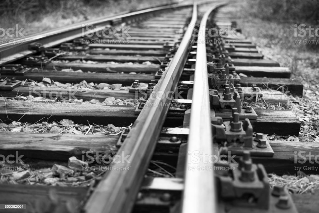 Rails to infinity.Hopeless post apocalyptic landscape. Cemetery of abandoned broken trains. Monochrome photo. stock photo