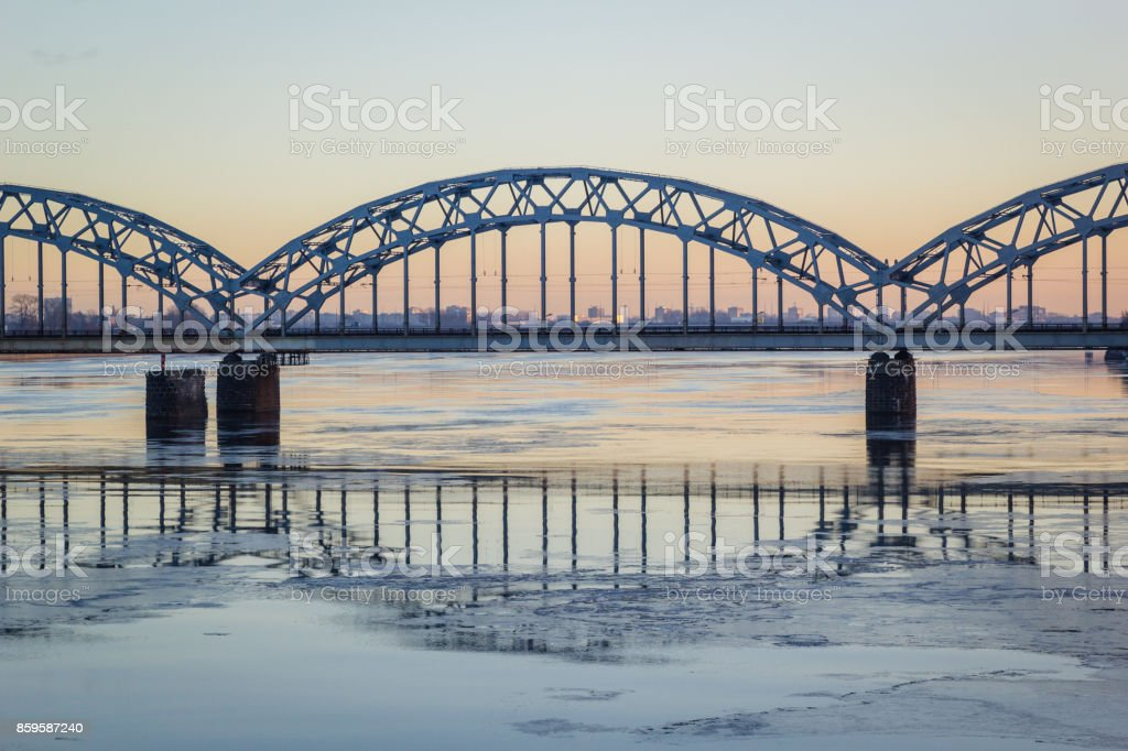 Railway bridge over frozen river in snowy winter Riga during sunset royalty-free stock photo