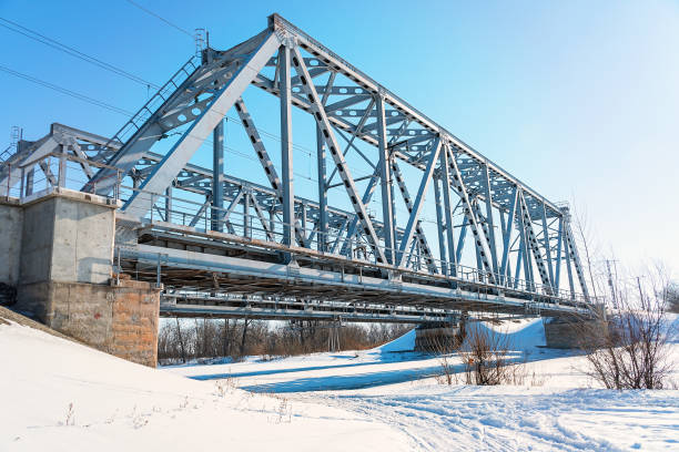 Railway bridge over the frozen river Railway bridge over the frozen river against the blue sky railway bridge stock pictures, royalty-free photos & images
