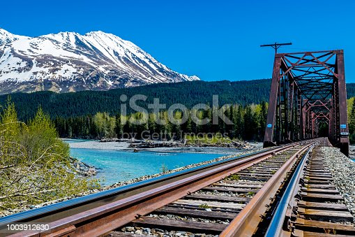Railway bridge over the turquoise Snow river with the Andy Simons mountain in background, Alaska.