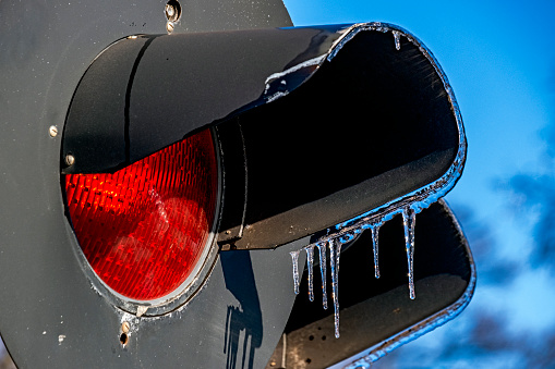 STOP!: Railway Colour Light Signal at Red with icicles hanging from sun visor/hood: winter, ice, after ice storm, cold, frozen