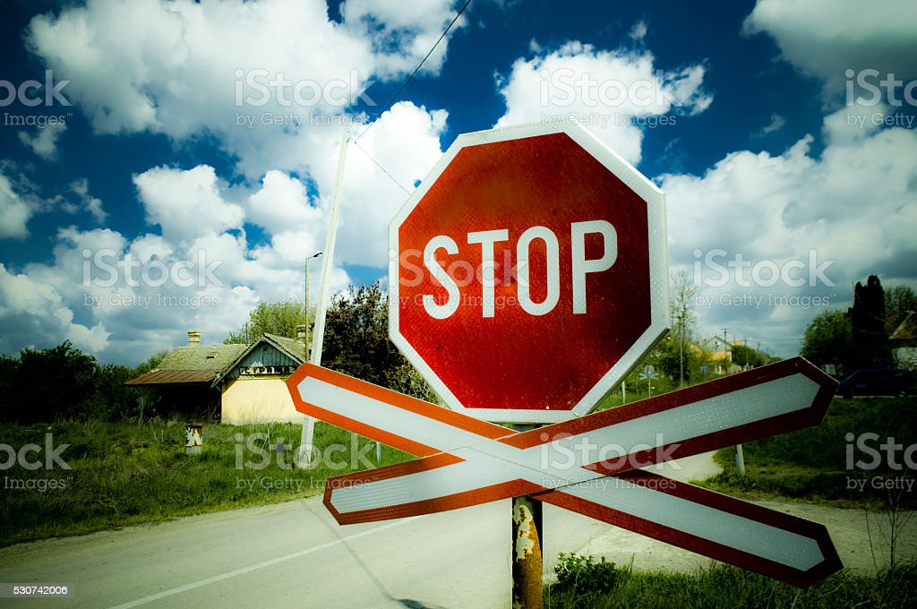 Railway crossing with St. Andrew's cross and stop sign stock photo