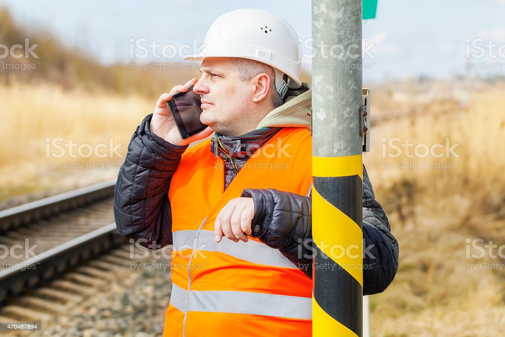 Railway employee talking on cell phone near railway stock photo