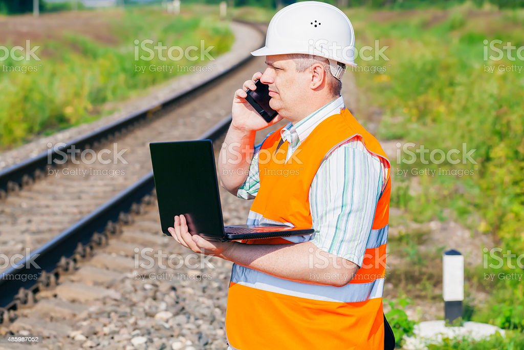 Railway Engineer with smartphone and laptop near railway stock photo