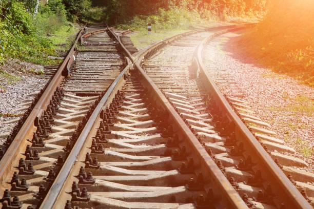 Eisenbahnknotenpunkt zwischen grünen Pflanzen an einem sonnigen Tag. Die Ehre der Schienen endet, einer der Äste geht steil zur Seite. Lebenswandelkonzept. – Foto