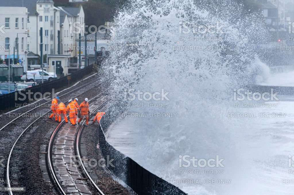 Railway maintenance crew repairing railway track after storm damage stock photo