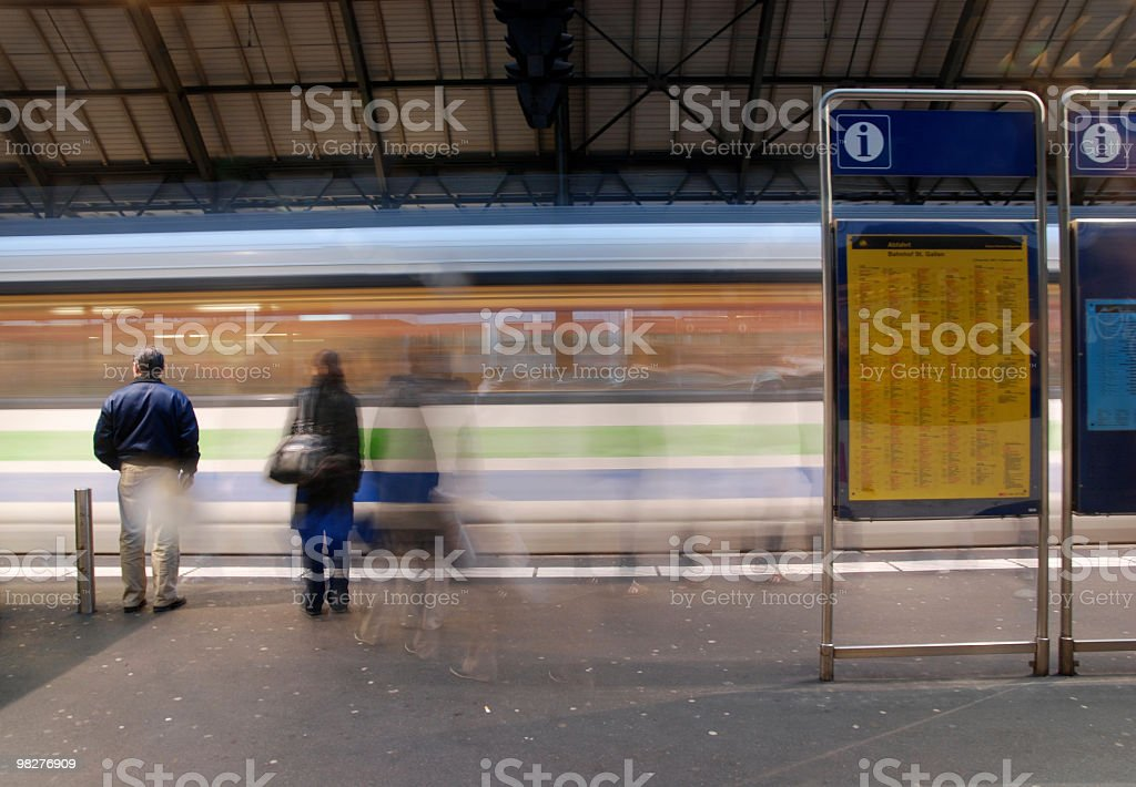 railway platform with incoming train and waiting passenger royalty-free stock photo