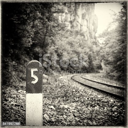 Square composition sepia toned color photography of selective focus of a railway sign, pole at ground level with the number 5 printed on top section, with an empty railroad, railway track in middle of lush foliage forest, along a rock cliff in nature, blurred in background. This picture was is retro styled with some vignette and cracked border.