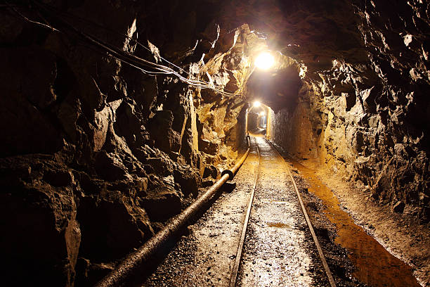 railway running through dimly lit mine shaft - dimly stock pictures, royalty-free photos & images