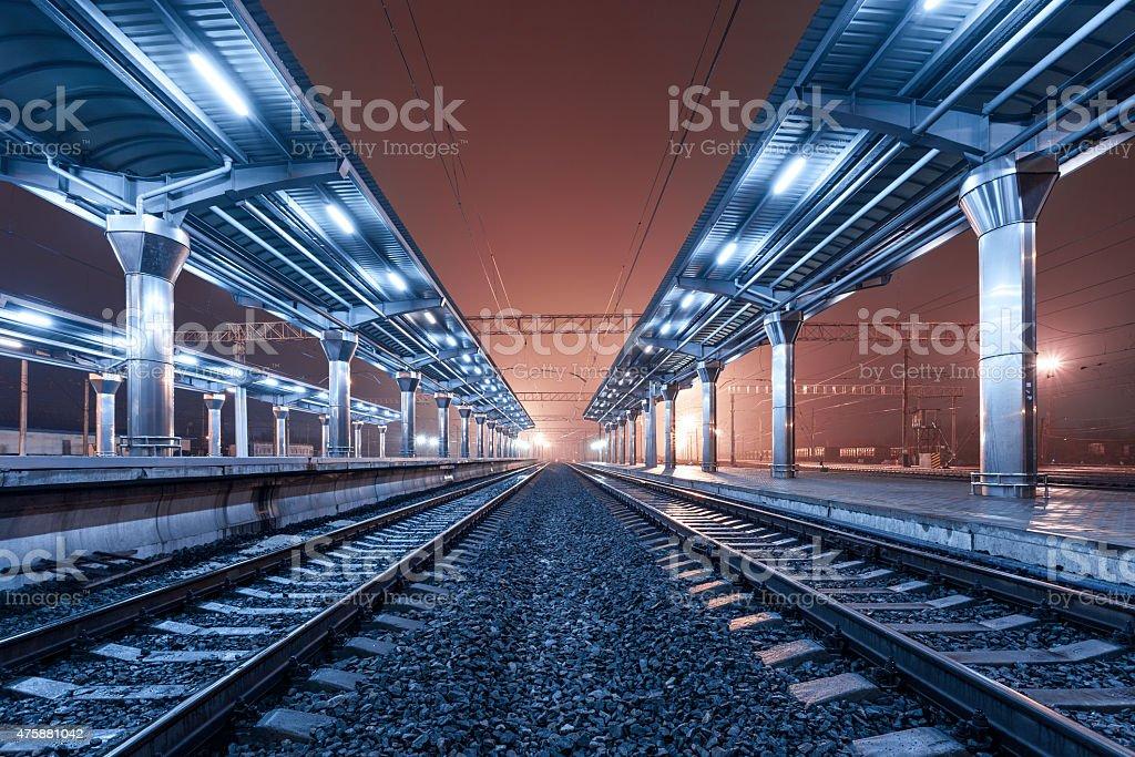 Railway station at night. Train platform in fog. Railroad in Donetsk.