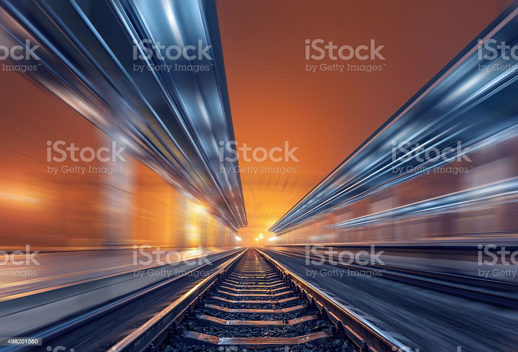Railway station at night with motion blur effect. Railroad stock photo