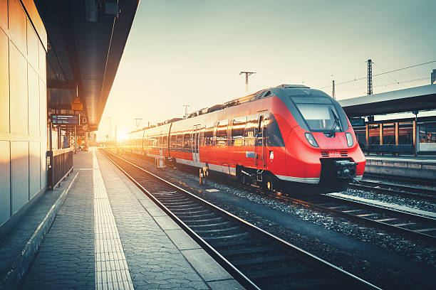 railway station with beautiful modern red commuter train at suns - train photos et images de collection