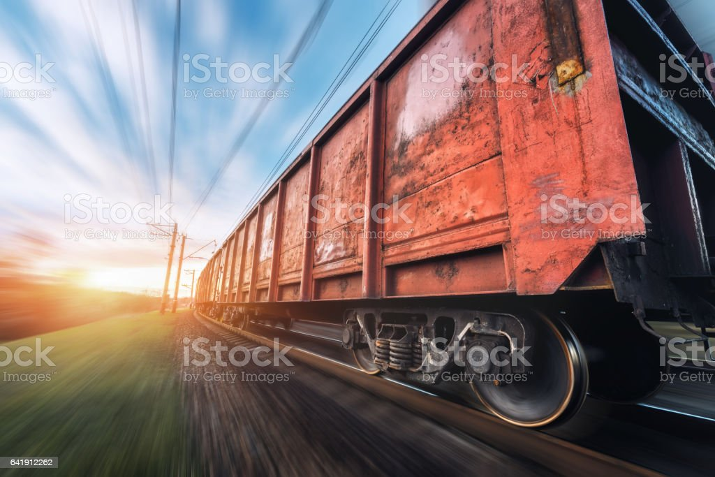 Railway station with cargo wagons and train in motion stock photo