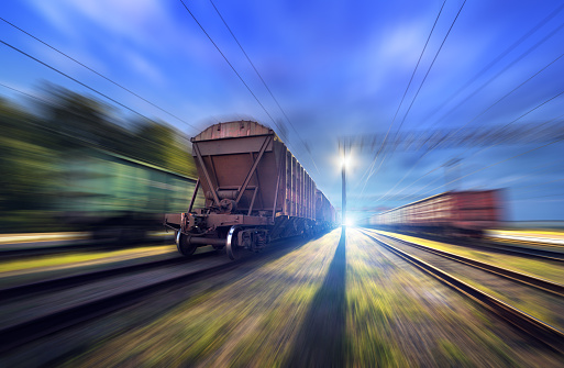 Railway station with cargo wagons and train light in motion