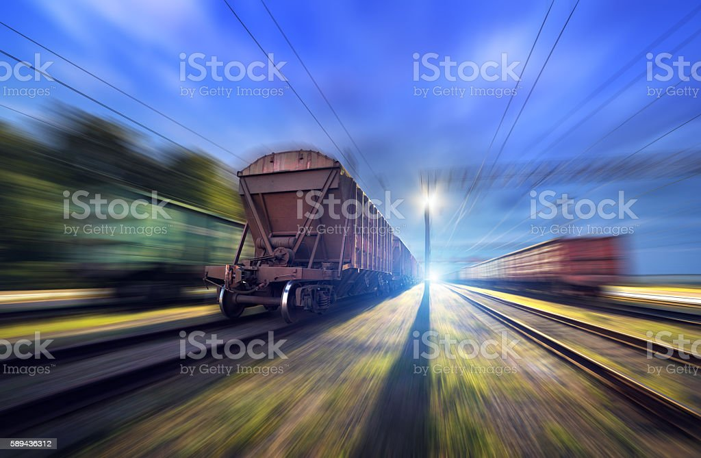 Railway station with cargo wagons and train light in motion stock photo