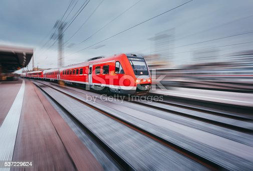 Railway station with modern high speed red passenger train at sunset in Nuremberg, Germany. Railroad with motion blur effect vintage toning. Industrial landscape