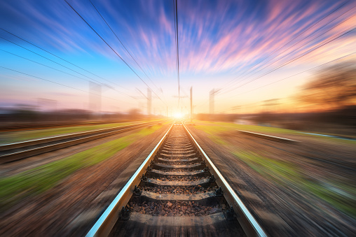 Railway station with motion blur effect at sunset. Blurred railroad. Industrial conceptual landscape with blurred railway station, blue sky with pink clouds and sunlight. Railway track in summer