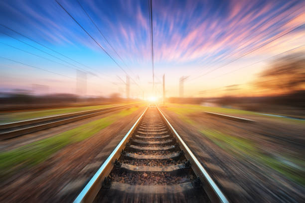 railway station with motion blur effect at sunset. blurred railroad. industrial conceptual landscape with blurred railway station, blue sky with pink clouds and sunlight. railway track in summer - den belitsky foto e immagini stock