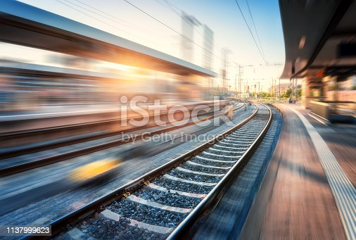 Railway station with motion blur effect at sunset. Industrial landscape with railroad, blurred railway platform, sky with orange sunlight in the evening. Railway junction in Europe. Transportation