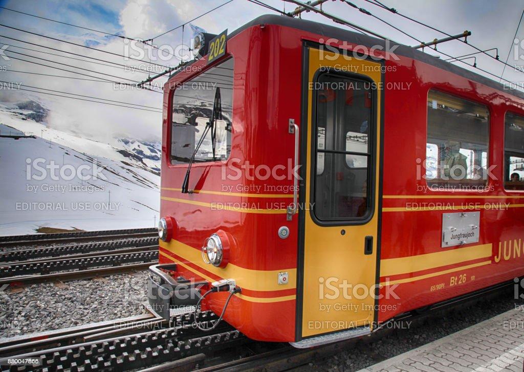 Railway station with red swiss train in Jungfrau, Switzerland. stock photo