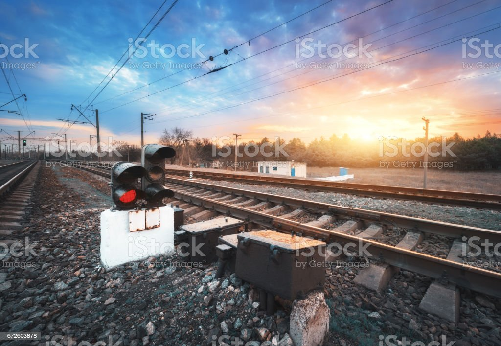 Railway station with semaphore and beautiful bright cloudy sky at sunset. Colorful industrial landscape. Railroad. Railway platform with traffic light. Heavy industry. Cargo shipping. Freight platform stock photo