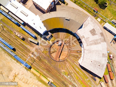 Aerial view to railway station with trains and engine house. Flight over tracks in Pilsen. Transportation and travel from above. Czech Republic, European Union.