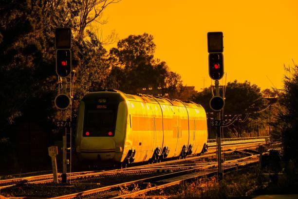 Puesta de sol de tren con los viajeros modernos tren pasando por una estación con semáforos - foto de stock