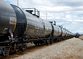 Black railway tanker cars of the type used to transport petroleum products. Several cars visible on two separate sets of tracks. Identification markings have been removed, only technical infomation remains.